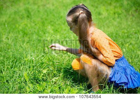 Blond girl catches a grasshopper in the grass