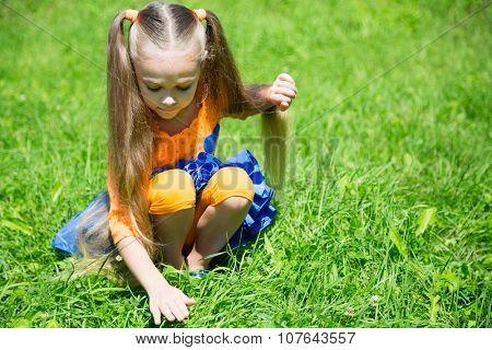 Cute little girl catches a grasshopper in the grass