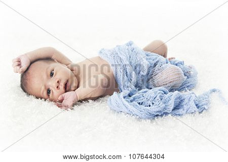 An adorable newborn stretching on a fluffy white  blanket and covered in a soft blue cheese cloth.  On a white background.