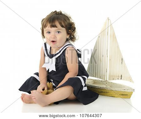 An adorable toddler sitting pretty in her sailor dress in front of a toy sailboat.  On a white background.