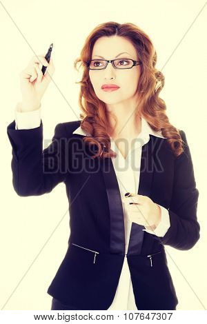 Businesswoman writing something on abstract screen.