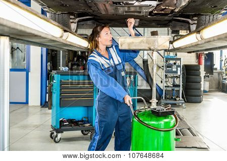 Female mechanic repairing car on hydraulic lift in automobile shop