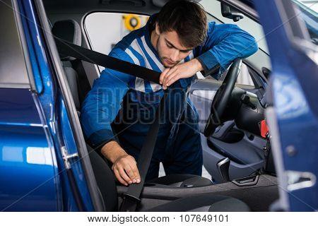 Male mechanic examining car seat belt in garage
