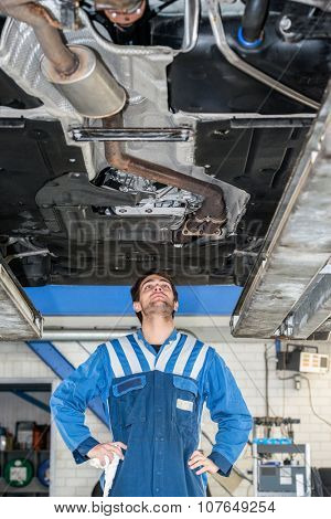 Male mechanic examining under the car at repair garage