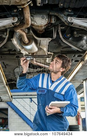 Male mechanic examining exhaust system of car with flashlight at auto repair shop