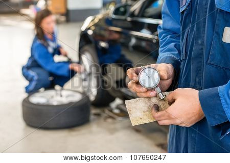 Midsection of mechanic holding analog gauge with colleague repairing car in background at garage