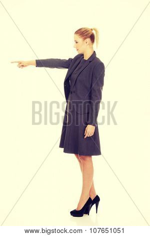 Young beautiful businesswoman pointing aside.