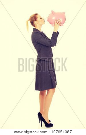 Happy business woman kissing piggybank.