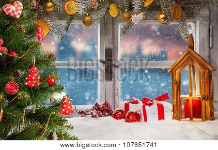 Atmospheric Christmas window sill decoration with beautiful sunset view. Christmas tree on foreground