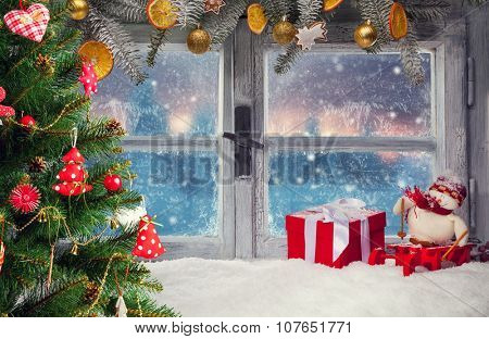 Atmospheric Christmas window sill decoration with beautiful sunset view.Christmas tree on foreground