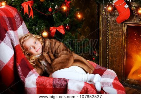 Cute little girl in a fur coat sitting in a room decorated for Christmas.