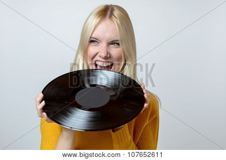 Happy Young Woman Biting A Vinyl Record