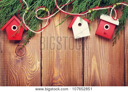 Christmas fir tree and birdhouse decor on rustic wooden board with copy space. Toned