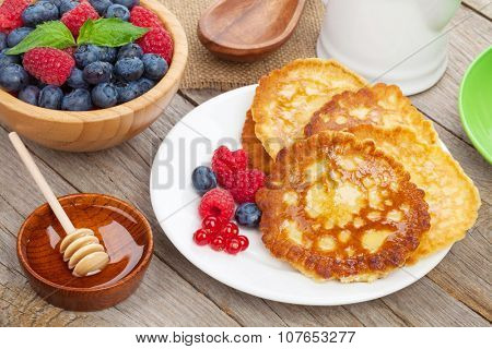 Pancakes with raspberry, blueberry, mint and honey syrup. On wooden table