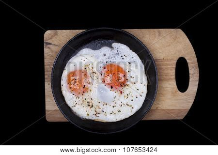 Scrambled eggs in iron skillet, top view isolated black