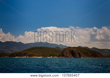 View Of Hilly Islands Azure Sea Against Blue Sky Cumulus Clouds