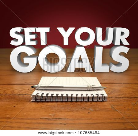 Seet Your Goals words in 3d letters above a notepad and pen for you to write missions, objectives or wishes in a list