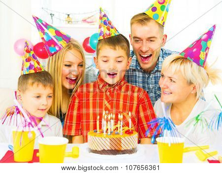 Birthday. Little boy blows out candles on birthday cake at party, Happy big family celebrating birthday of kid