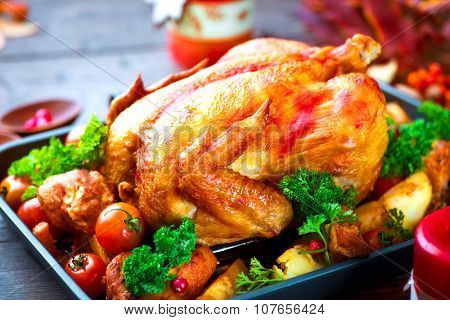 Roasted Turkey garnished with Potato, Vegetables and cranberries on a rustic style table decorated with autumn leaves and candles. Thanksgiving or Christmas Dinner