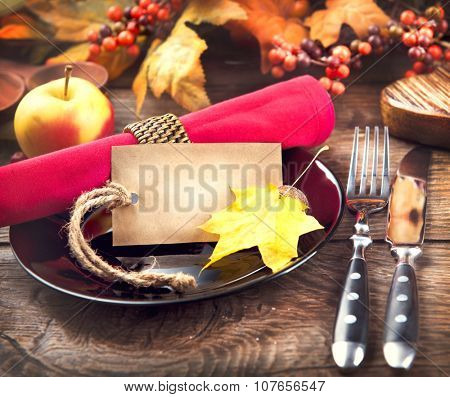 Thanksgiving Dinner. Thanksgiving wooden table served, decorated with bright autumn leaves. Holiday Table setting with greeting blank card