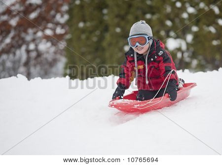 Little boy sledding.