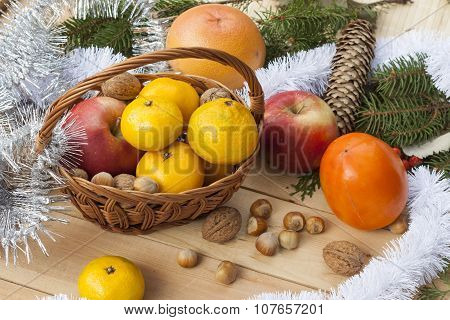 Tangerines, apple and nuts wickerwork hamper in Christmas decor with Christmas tree, nuts and apples