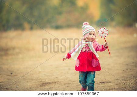 little girl playing pinwheel toy walking on autumn landscape