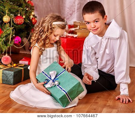 Children  receiving gifts under Christmas tree. Vintage style.