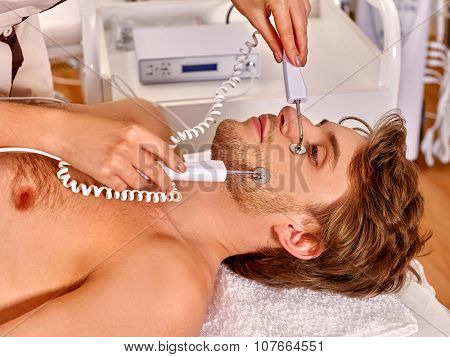 Man receiving electric galvanization facial hydradermie at beauty salon.