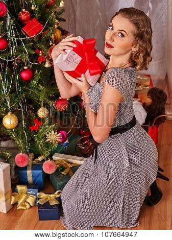 Woman receiving gifts under Christmas tree. BVintage style.
