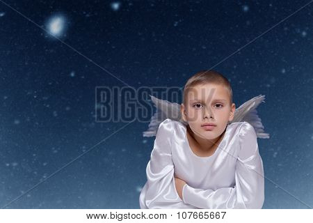 angel child against falling snow background on christmas night