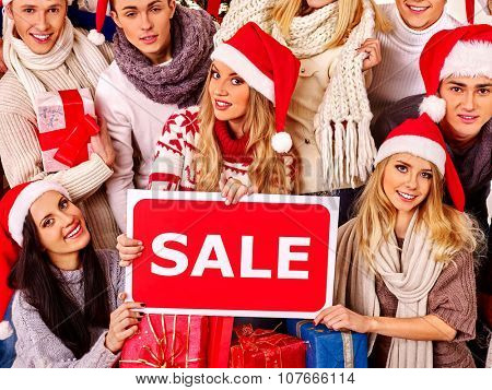 Women and young men in Santa hat holding sign saying sale and gift box.