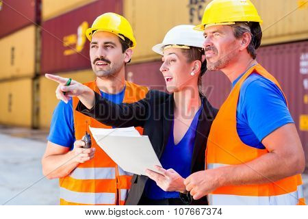 Workers on logistics container port discussing freight or shipment documents