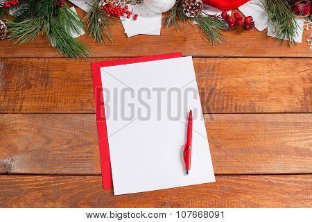 The blank sheet of paper on the wooden table with a pen