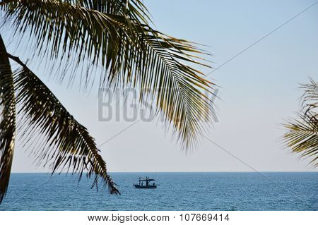 fishery boat on the sea behind coconut leaf