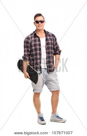 Full length portrait of a male skater holding a skateboard and looking at the camera isolated on white background