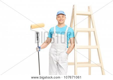 Young painter holding a paint roller and leaning against a wall isolated on white background