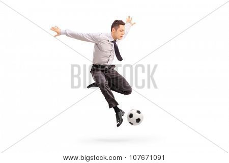 Young businessman shot in mid-air just about to kick a football isolated on white background
