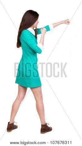 skinny woman funny fights waving his arms and legs. Isolated over white background. The girl in a dress beats foot in brown shoe. The girl in the green dress has a strict right hand.