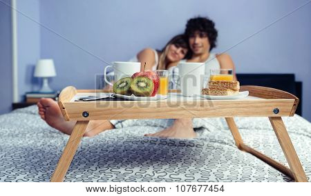 Healthy breakfast on tray and couple lying in background