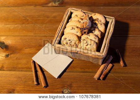 christmas,  baking, culinary, holidays and food concept - close up of oat cookies in wooden box with blank greeting card and cinnamon on table