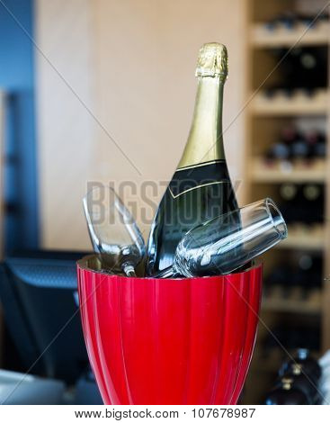drink, holidays, celebration, alcohol and objects concept - close up of champagne bottle and glasses cooling in ice bucket at restaurant