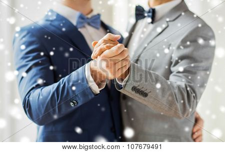 people, homosexuality, same-sex marriage and love concept - close up of happy male gay couple holding hands and dancing on wedding over snow effect