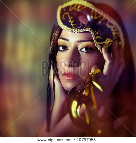 Portrait of beautiful brunet woman wearing gold Venetian mask over colorful background, luxury masquerade party on New Year eve, perfect holiday makeup, fashion portrait