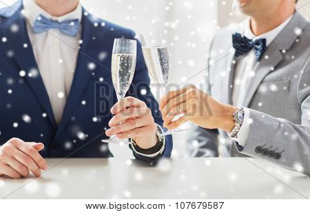 people, celebration, homosexuality, same-sex marriage and love concept - close up of happy married male gay couple in suits and bow-ties drinking sparkling wine on wedding over snow effect