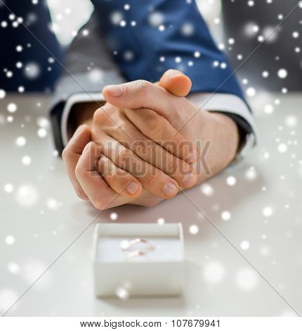 people, homosexuality, same-sex marriage and love concept - close up of happy male gay couple holding hands and wedding rings in box on table over snow effect