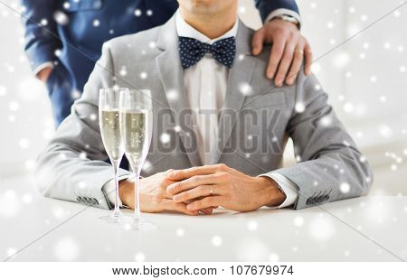 people, celebration, homosexuality, same-sex marriage and love concept - close up of married male gay couple in suits with sparkling wine glasses putting hand on shoulder on wedding over snow effect