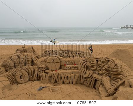Gijon, Spain - October 24, 2015: Surfer Goes Behind The Sand Sculptures On The Beach Of San Lorenzo,