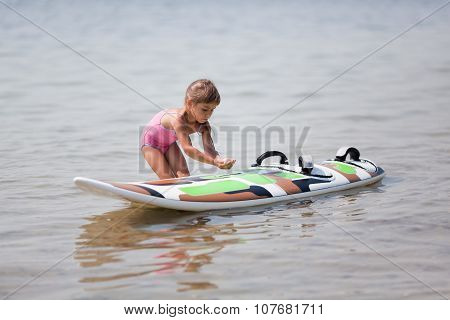 Little Girl And Windsurfing Board