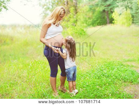Happy Pregnant Woman, Little Child Daughter Kissing Tummy Mother In Summer Day